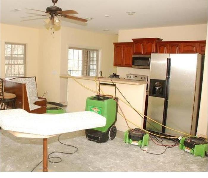 kitchen with concrete subfloor and green SERVPRO equipment setup