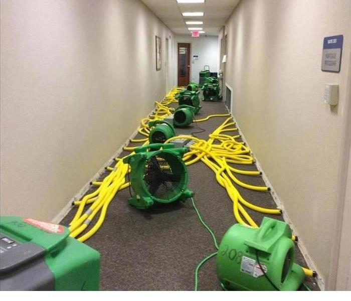 servpro airmovers plugged in and drying out the carpet