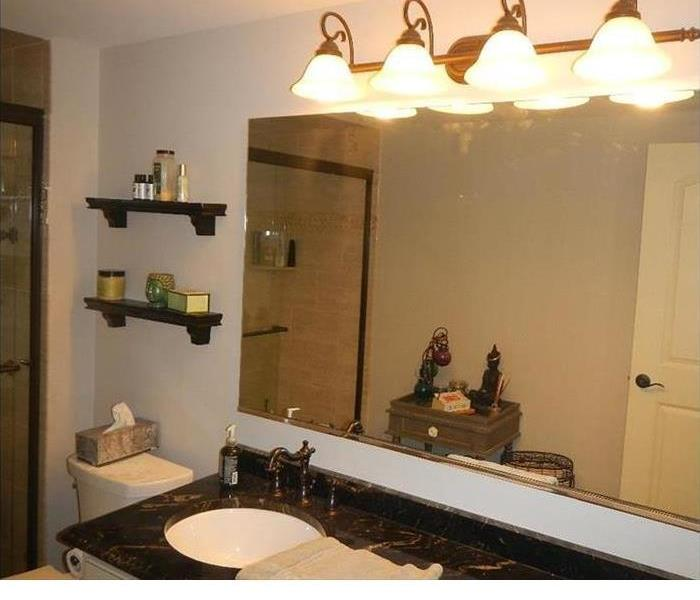 a bathroom with lights above the sink mirror that has ben restored