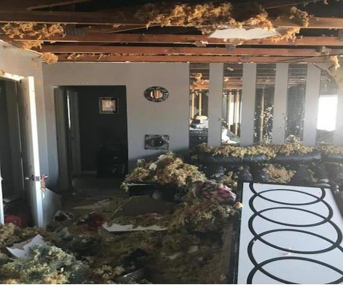 fire damage in a home with the insulation and other items in the wall and ceiling falling out
